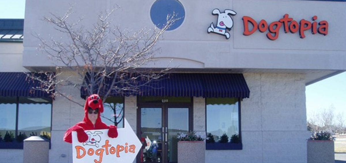 Dogtopia employee standing with advertisement sign for the company - a sign of high employee engagement through commitment.