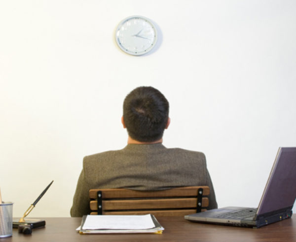 Man in office staring at clock (clock-watching), showing lack of care for his work; an indication of low employee engagement